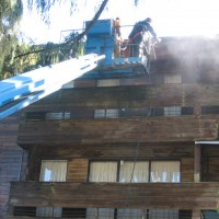 BEFORE - dirty wooden siding being washed from a hydraulic lift, in Burnaby