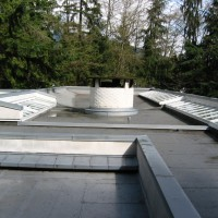 A flat torch-on roof cleaned with scuppers and downpipe drains
