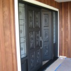 siding boards stained and front doors painted