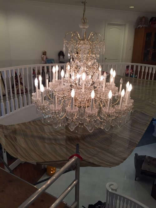 dirty crystal chandelier during cleaning by A Glass Act